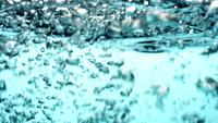 Scene-of-waves-and-bubbles-floating-in-blue-liquid-in-4k