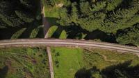 Drone ascending above a viaduct in a forest