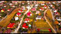 Drone view on houses in a village - tilt shift effect in 4K