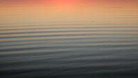Kalme rollende golven die op de zonsondergang wijzen