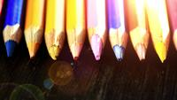 On a wooden background multi-colored pencils. Bright colored pencils Close up. Macro. Macro shooting