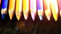 På en träbakgrund med flerfärgade pennor. Ljusfärgade pennor Närbild. Makro. Makrofotografering