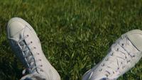 Schließen Sie oben von den weißen Turnschuhen auf dem Gras