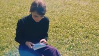 Kvinna söker en bok i sin väska och sitter på gräset