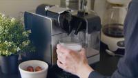 Mulher faz seu café expresso com a máquina dela