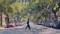 Zwei Frauen überqueren die Straße von links nach rechts