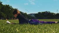 Un tiro de ángulo bajo de mujer descansando en la hierba y relajándose con un libro