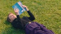 Kvinna söker en bok i sin väska och slappnar av på gräset