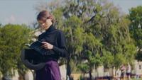 Una toma panorámica de una mujer leyendo un libro azul en el parque