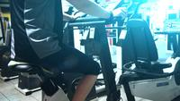 A girl exercising on a stationary bike in a gym.