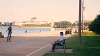 Man Reading in Queens Landing With Shedd Aquarium in Background