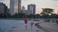 Couple Walking On A Dock Of Chicago With Buildings In Background