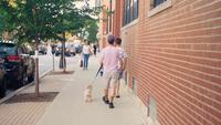 Människor och liten hund som går på trottoaren i Chicago