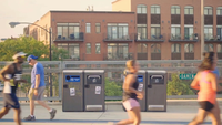 Runners And Cyclists On Footbridge With Trash Containers