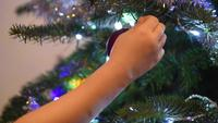 A child hanging an ornament onto the christmas tree