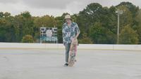 Junger Mann mit Hut, der sein Skateboard aufhebt