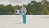 Joven con sombrero caído y recogiendo su patineta