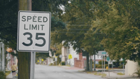 Handheld Clip Of A Speed Limit Sign In Urban Landscape