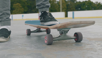 Close Up Of A Man Picking Up His Skateboard And Spinning It