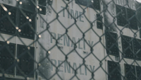 Detail einer Sportanzeigetafel angesehen durch ein schwarzes Gitter