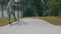 Junger Mann, der auf eine kleine Rampe in einem Skate-Park eisläuft