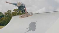 Young Man Making A Trick Climbing A Concrete Ramp