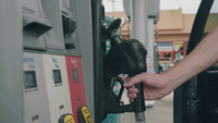 Man In Filling Station Taking A Nozzle From Fuel Dispenser