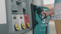 Man In Filling Station Placing A Nozzle In Fuel Dispenser