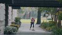 Young Woman On Her Longboard Approaching On The Sidewalk