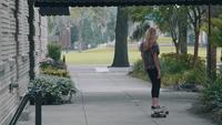 Junge Frau auf ihrem Longboard, der weg auf dem Bürgersteig verschiebt