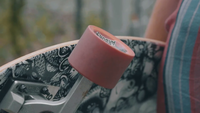Close Up Of Woman Rolling A Wheel Of Her Longboard