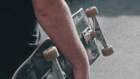 Detail Of Man Walking And Holding His Skateboard