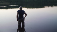 Plano medio de la vieja dama en el lago mirando el bosque