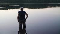 Plan moyen de la vieille dame dans le lac en regardant la forêt