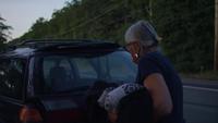 Alte Dame, die Kleidung in ihr Auto in Zeitlupe einsetzt