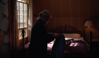 Handheld Clip Of Old Lady Folding Laundry On Her Bed