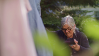 Handheld Clip van oude dame oppakken van kleding