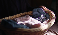 Close Up Of Old Lady Holding Her Laundry Basket And Folding Clothes