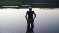 medium skott av gammal dam som går in i sjön