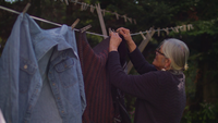 Old Lady Hanging Sweaters In Slow Motion