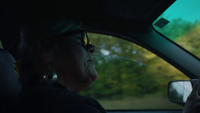 Close Up Of Old Lady Driving And Speaking With A Passenger