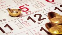 Close Up Of Man Placing A Gold Ingot On Calendar