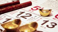 Close Up Of Man Placing A Chinese Gold Ingot On Calendar