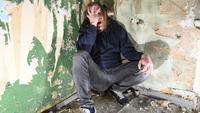 Depressief en boos man zit in de hoek in een verlaten huis