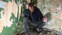 Depressed and angry man is sitting in the corner in an abandoned house