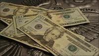 Rotating stock footage shot of American paper currency on an American eagle shield background - MONEY 0392