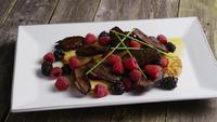 Foto giratoria de un delicioso plato de tocino de pato ahumado con piña a la parrilla, frambuesas, moras y miel - COMIDA 094