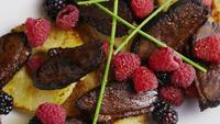 Foto giratoria de un delicioso plato de tocino de pato ahumado con piña a la parrilla, frambuesas, moras y miel - COMIDA 093