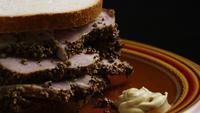 Rotating shot of delicious, premium pastrami sandwich next to a dollop of dijon mustard - FOOD 042
