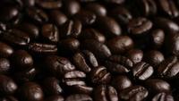 Foto giratoria de deliciosos granos de café tostados sobre una superficie blanca - CAFÉ HABAS 017